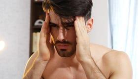 Hombre joven que despierta con dolor de cabeza Imagen de archivo