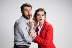 Hombre joven que dice chismes a su colega de la mujer en la oficina Foto de archivo