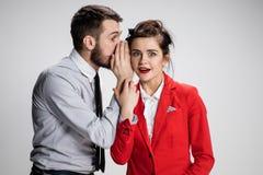 Hombre joven que dice chismes a su colega de la mujer en la oficina Fotografía de archivo libre de regalías