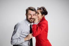 Hombre joven que dice chismes a su colega de la mujer en la oficina Fotos de archivo