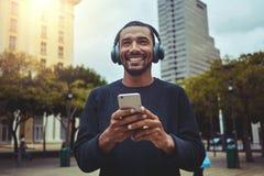 Hombre joven que disfruta de la música en el auricular a través del teléfono móvil imagenes de archivo