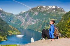 Hombre joven que disfruta de la visión cerca del fiordo de Geiranger, Noruega Imagen de archivo libre de regalías