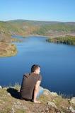 Hombre joven que disfruta de la vista de un lago hermoso Foto de archivo libre de regalías