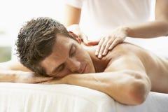 Hombre joven que disfruta de masaje en el balneario Imagen de archivo libre de regalías