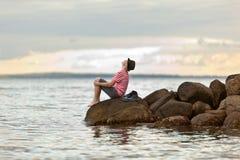 Hombre joven que disfruta de una puesta del sol del océano Imagen de archivo