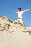 Hombre joven que disfruta del día de fiesta de la playa que se ejecuta abajo de la duna Foto de archivo
