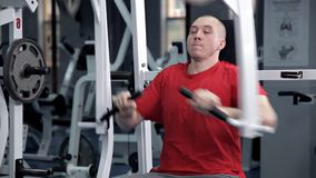 Hombre joven que dobla sus músculos del pecho en el simulador Salud, deporte almacen de metraje de vídeo