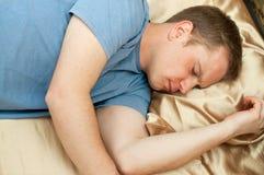 Hombre joven que duerme en cama Imagen de archivo libre de regalías