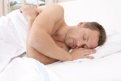 Hombre joven que duerme en cama. Imagen de archivo libre de regalías