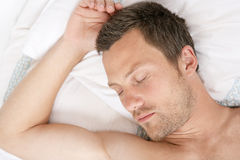 Hombre joven que duerme en cama. fotografía de archivo libre de regalías