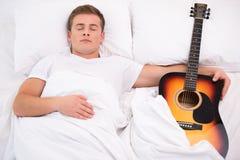 Hombre joven que duerme en cama con la guitarra Imágenes de archivo libres de regalías