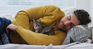 Hombre joven que duerme en el sofá que sostiene su gato del animal doméstico en sus brazos 4K 4k almacen de metraje de vídeo
