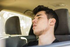 Hombre joven que duerme en la rueda que conduce su coche Foto de archivo