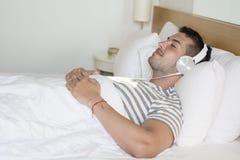 Hombre joven que duerme en música que escucha de la cama Imágenes de archivo libres de regalías