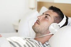 Hombre joven que duerme en música que escucha de la cama Fotografía de archivo libre de regalías