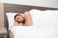 Hombre joven que duerme pacífico en su propia cama Imágenes de archivo libres de regalías