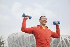 Hombre joven que ejercita con pesas de gimnasia en el parque, Pekín Fotografía de archivo libre de regalías