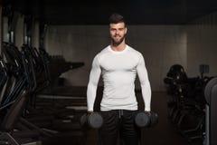 Hombre joven que ejercita el bíceps con pesas de gimnasia Imágenes de archivo libres de regalías