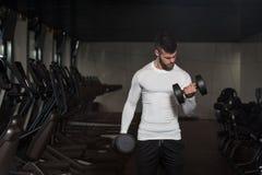 Hombre joven que ejercita el bíceps con pesas de gimnasia Foto de archivo