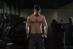Hombre joven que ejercita el bíceps con pesas de gimnasia Fotos de archivo