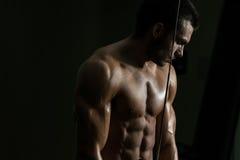 Hombre joven que ejercita el tríceps en el gimnasio Imágenes de archivo libres de regalías