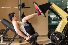 Hombre joven que ejercita en la prensa de la pierna durante entrenamiento de la parte inferior del cuerpo imagen de archivo