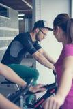Hombre joven que ejercita en las bicis inmóviles Fotografía de archivo libre de regalías