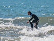 Hombre joven que ejercita en practicar surf en el tablero Imagen de archivo libre de regalías