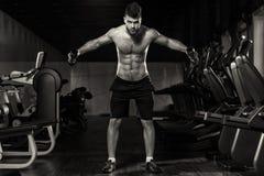Hombre joven que ejercita hombros con pesas de gimnasia Fotos de archivo libres de regalías