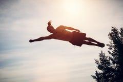 Hombre joven que eleva y mantiene flotando en el aire fotos de archivo