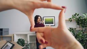 Hombre joven que elige el lugar para la imagen mientras que novia que le ayuda que gesticula metrajes