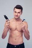 Hombre joven que elige la maquinilla de afeitar Imagen de archivo