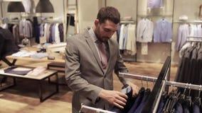 Hombre joven que elige la ropa en tienda de ropa almacen de video