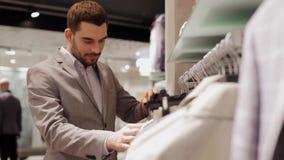 Hombre joven que elige la ropa en tienda de ropa metrajes