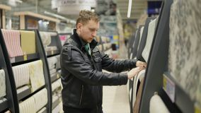 Hombre joven que elige los papeles pintados en supermercado Él está mirando el papel pintado, lo está tocando y está pensando cuá almacen de video