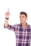 Hombre joven que empuja el botón Foto de archivo