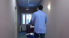 Hombre joven que empuja un carro de la economía doméstica con las toallas limpias en un hotel almacen de video