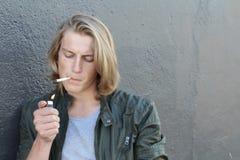 Hombre joven que enciende un primer del cigarrillo con las porciones de espacio de la copia Foto de archivo libre de regalías