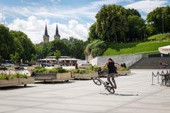 Hombre joven que engaña en BMX en el cuadrado en Tallinn, Estonia Fotos de archivo