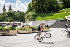 Hombre joven que engaña en BMX en el cuadrado en Tallinn, Estonia Imagenes de archivo
