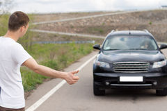 Hombre joven que engancha una elevación en una carretera nacional Imagen de archivo