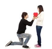 Hombre joven que entrega el regalo del amor a la mujer joven Fotos de archivo libres de regalías