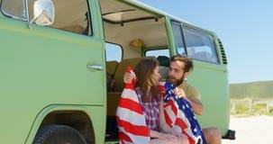 Hombre joven que envuelve a la mujer hermosa con la bandera americana 4k almacen de video