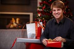Hombre joven que envuelve los regalos en la Navidad Imagen de archivo libre de regalías