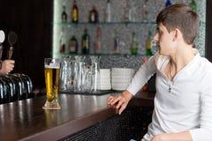 Hombre joven que es servido una pinta de cerveza Fotos de archivo libres de regalías