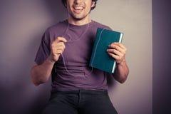 Hombre joven que escucha el libro audio Imágenes de archivo libres de regalías