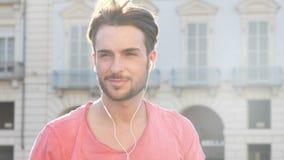 Hombre joven que escucha la música con los auriculares almacen de metraje de vídeo
