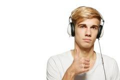 Hombre joven que escucha la música en el auricular imagen de archivo