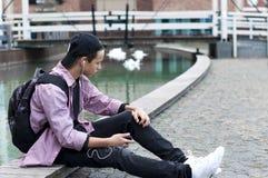 Hombre joven que escucha la música que se sienta en la acera Foto de archivo libre de regalías