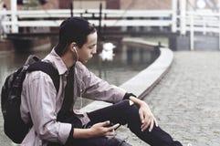 Hombre joven que escucha la música que se sienta en la acera Foto de archivo